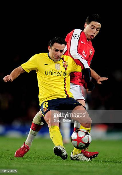 Xavi Hernandez of Barcelona is challenged by Samir Nasri of Arsenal during the UEFA Champions League quarter final first leg match between Arsenal...
