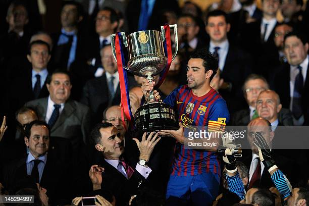 Xavi Hernandez of Barcelona is handed the Copa del Rey trophy by Prince Felipe after beating Athletic Bilbao 30 during the Copa del Rey Final at...