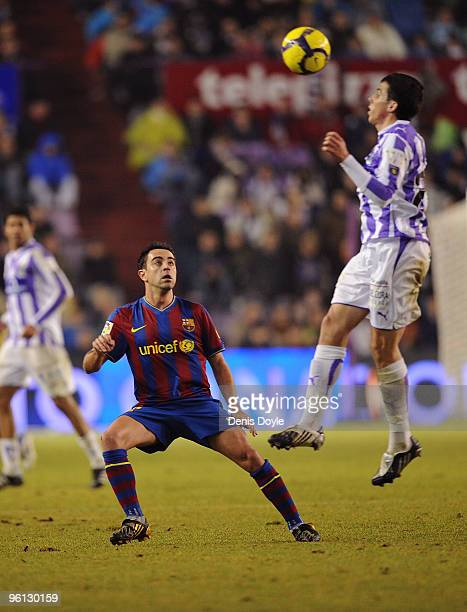Xavi Hernandez of Barcelona watches a Valladolid player head a long ball during the La Liga match between Valladolid and Barcelona at the Jose...