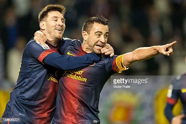 Xavi Hernandez of FC Barcelona celebrates with his teammate Lionel Messi after scoring against Real Valladolid during the La Liga game between Real...