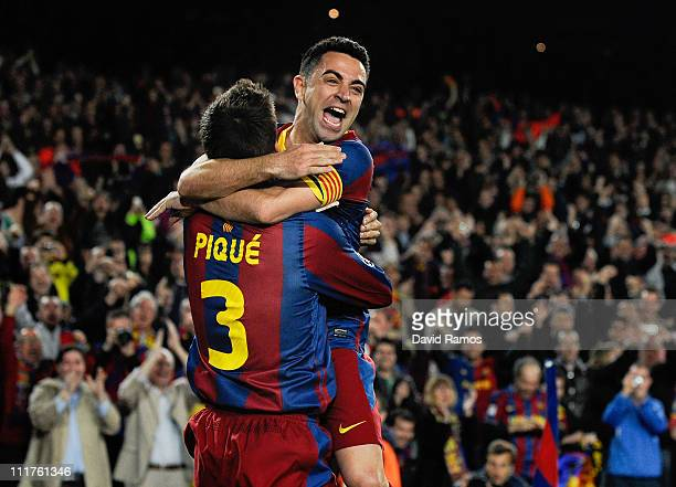 Xavi Hernandez of FC Barcelona celebrates with teammate Gerard Pique after Pique scored their team's third goal during the UEFA Champions League...
