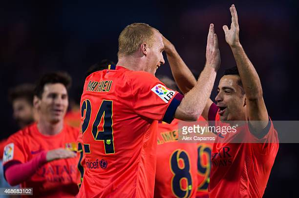 Xavi Hernandez of FC Barcelona congratulates his teammate Jeremy Mathieu after he scored the opening goal during the La Liga match between Celta Vigo...