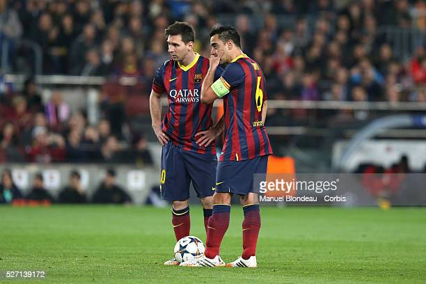 Xavi Hernandez of FC Barcelona covers his mouth with his hand to avoid lip reading as he speaks to Lionel Messi during the UEFA Champions league...