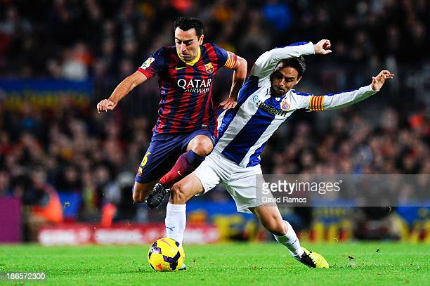Xavi Hernandez of FC Barcelona duels for the ball with Sergio Garcia of RCD Espanyol during the La Liga match between FC Barcelona and RCD Espanyol...