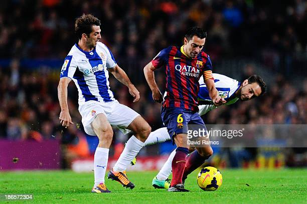 Xavi Hernandez of FC Barcelona duels for the ball with Victor Sanchez and Sergio Garcia of RCD Espanyol during the La Liga match between FC Barcelona...