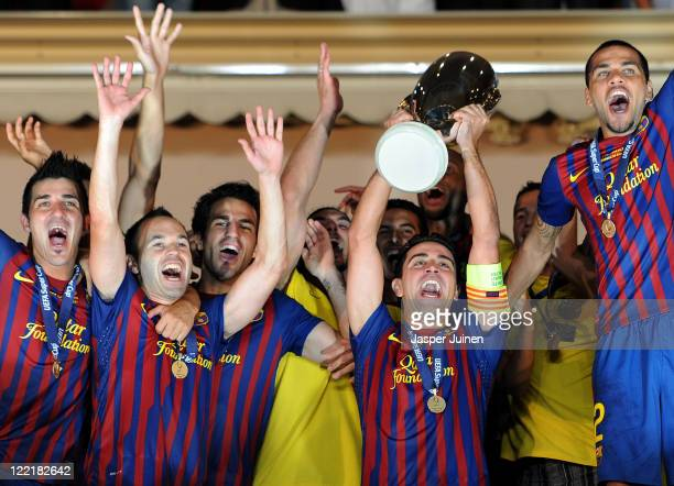 Xavi Hernandez of FC Barcelona holds the trophy aloft amid his teammates David Villa Andres Iniesta Cesc Fabregas and Daniel Alves during the UEFA...