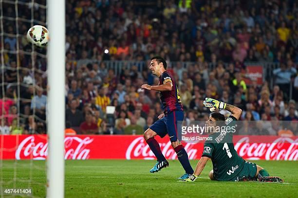 Xavi Hernandez of FC Barcelona scores the opening goal past Xabi Irureta of SD Eibar during the La Liga match between FC Barcelona and SD Eibar at...