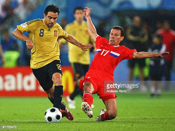 Xavi Hernandez of Spain is tackled by Konstantin Zyrianov of Russia during the UEFA EURO 2008 Semi Final match between Russia and Spain at Ernst...