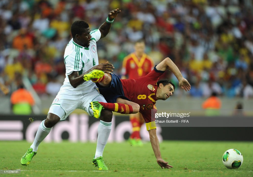 Xavi Hernandez of Spain is tripped by John Ugochukwu of Nigeria during the FIFA Confederations Cup Brazil 2013 Group B match between Nigeria and Spain at Castelao on June 23, 2013 in Fortaleza, Brazil.