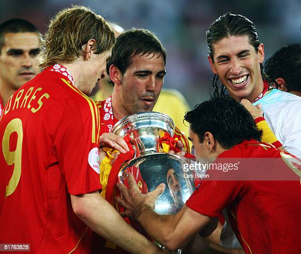 Xavi Hernandez of Spain looks at the trophy with team mates Fernando Torres Fernando Navarro and Sergio Ramos after the UEFA EURO 2008 Final match...
