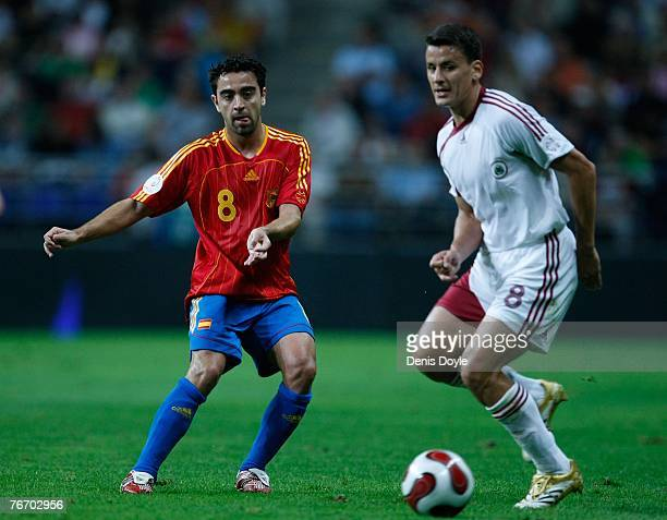 Xavi Hernandez of Spain slides the ball past Imants Bleidelis of Latvia during the UEFA Euro 2008 group F qualifier between Spain and Latvia at the...
