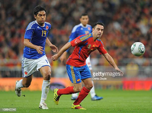 Xavi Hernandez of Spainv gets past Abel Aguilar of Colombia during the International friendly match between Spain and Colombia at Estadio Santiago...