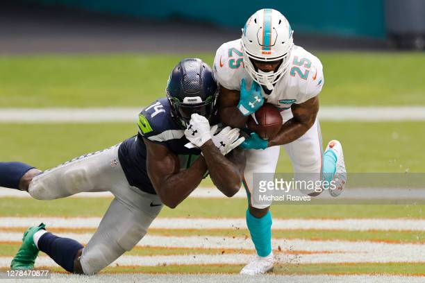 Xavien Howard of the Miami Dolphins intercepts a pass intended for DK Metcalf of the Seattle Seahawks during the third quarter at Hard Rock Stadium...
