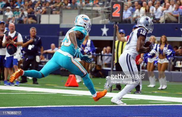 Xavien Howard of the Miami Dolphins pursues Amari Cooper of the Dallas Cowboys as he scores a touchdown in the first quarter at AT&T Stadium on...