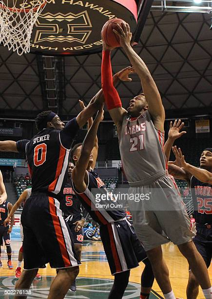 Xavier Adams of the New Mexico Lobos drives to the basket and tries to get past Horace Spencer of the Auburn Tigers at the Stan Sheriff Center during...