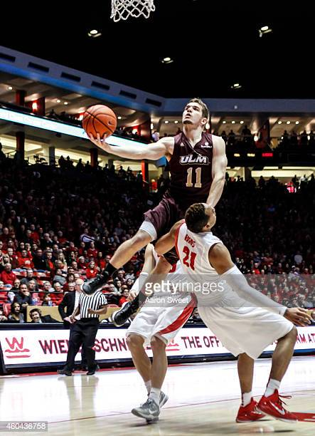 Xavier Adams of the New Mexico Lobos is fouled by Nick Coppola of the LouisianaMonroe Warhawks during their game at The WisePies Arena aka the Pit on...