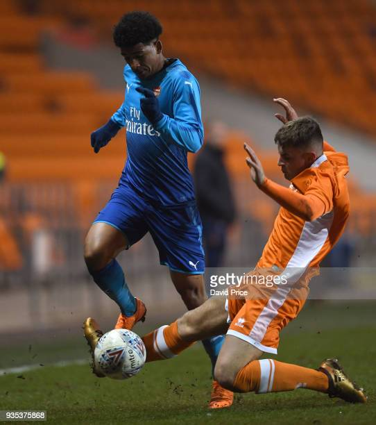 Xavier Amaechi of Arsenal is fouled by Jack Newton of Blackpool during the match between Blackpool and Arsenal at Bloomfield Road on March 20 2018 in...