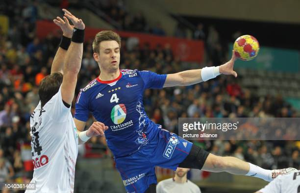 Xavier Barachet of France is blocked by Michael Haass of Germany the men's Handball World Championships main round match Germany vs France in...