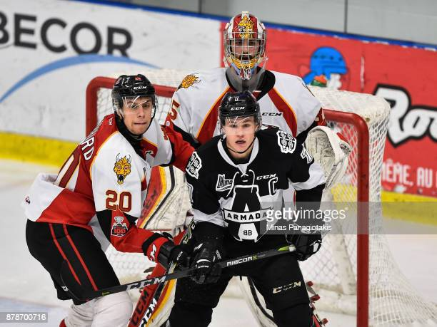 Xavier Bouchard of the BaieComeau Drakkar and Alexandre Alain of the BlainvilleBoisbriand Armada battle for position in front of goaltender Antoine...