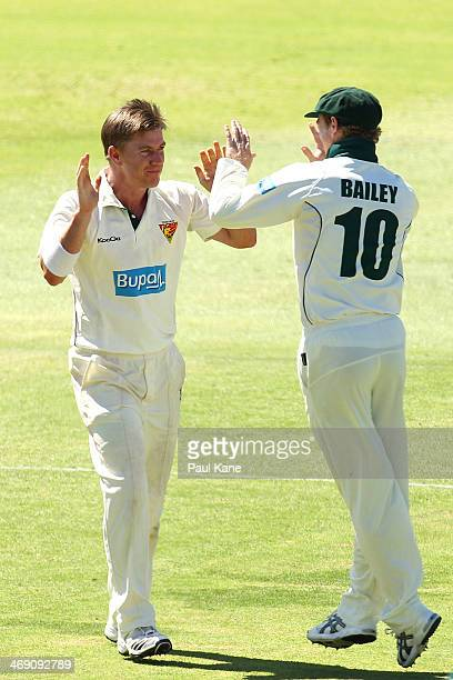 Xavier Doherty and George Bailey of the Tigers celebrate the wicket of Mitchell Marsh of the Warriors during day two of the Sheffield Shield match...