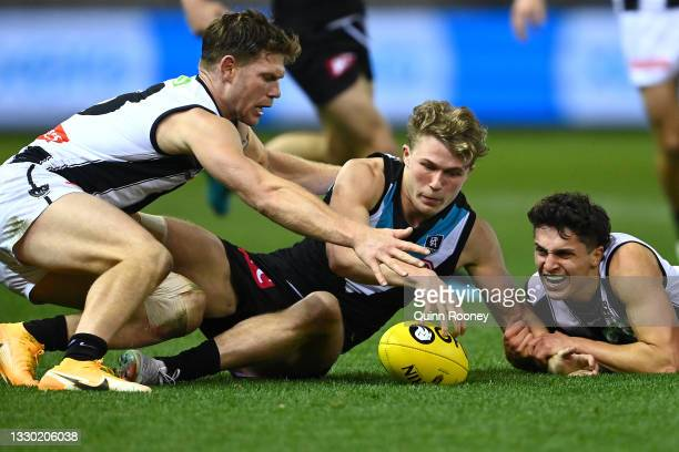 Xavier Duursma of the Power is tackled by Taylor Adams and Trent Bianco of the Magpies during the round 19 AFL match between Port Adelaide Power and...