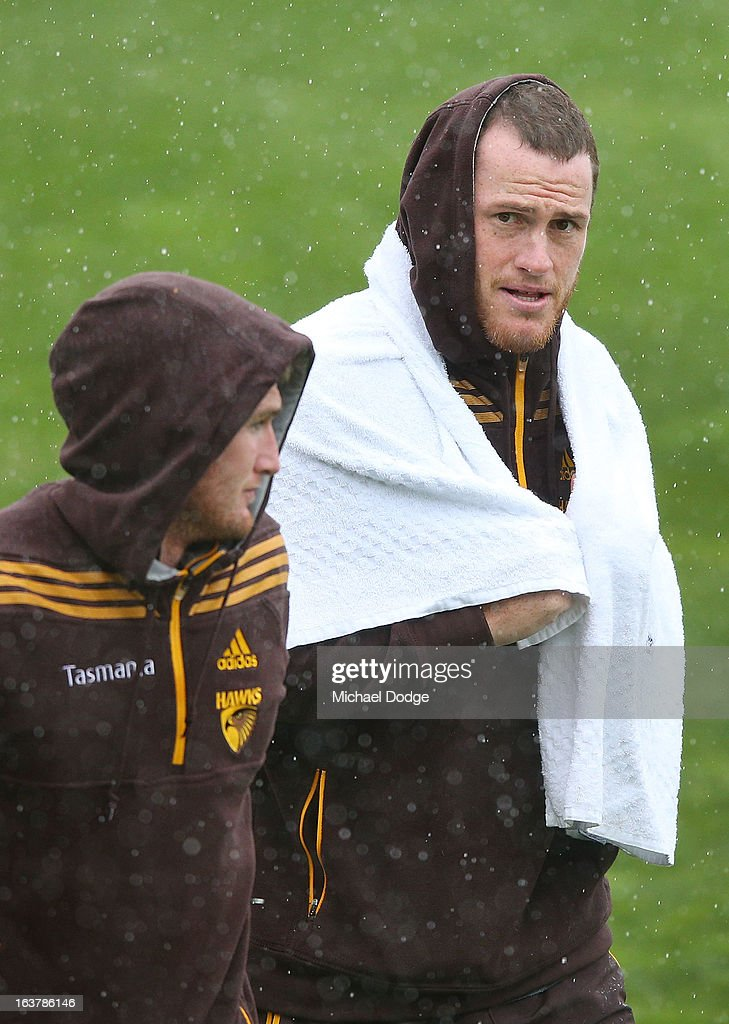 Xavier Ellis (L) and Jarryd Roughead of the Hawks walk off the ground after the game was called off due to the rain during the AFL NAB Cup match between the North Melbourne Kangaroos and the Hawthorn Hawks at Highgate Recreational Reserve on March 16, 2013 in Craigieburn, Australia.