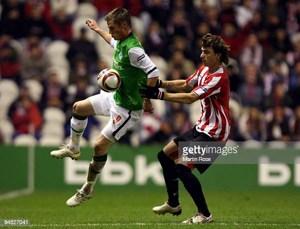 Xavier Etxeita of Bilbao and Markus Rosenberg of Bremen compete for the ball during the UEFA Europa League Group L match between Atletico Bilbao and...