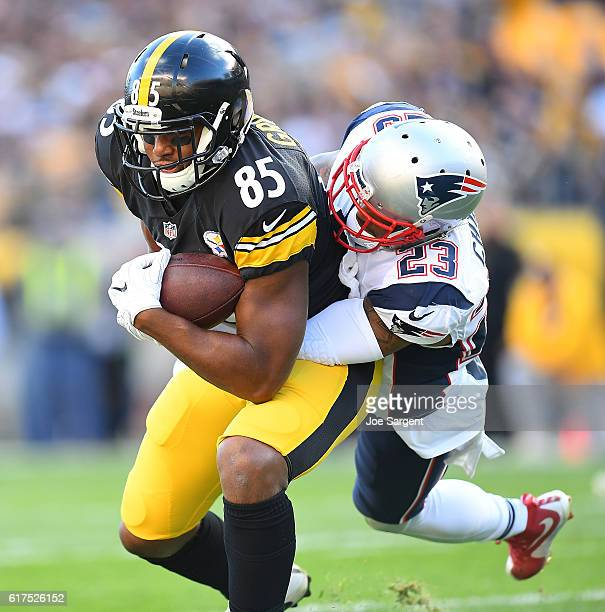 Xavier Grimble of the Pittsburgh Steelers is wrapped up by Patrick Chung of the New England Patriots after making a catch in the first quarter during...