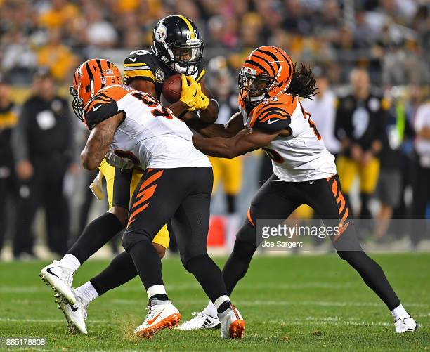 Xavier Grimble of the Pittsburgh Steelers makes a catch before being tackled by Vontaze Burfict and Josh Shaw of the Cincinnati Bengals in the second...