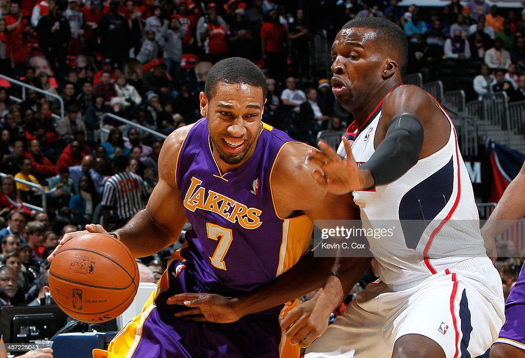Xavier Henry #7 of the Los Angeles Lakers drives against Shelvin Mack #8 of the Atlanta Hawks at Philips Arena on December 16, 2013 in Atlanta, Georgia.