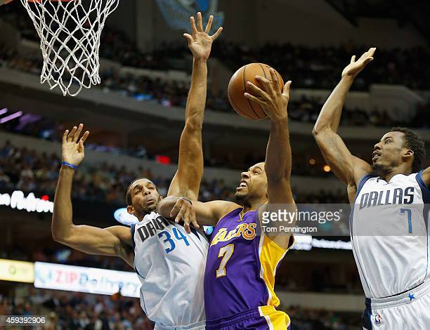 Xavier Henry of the Los Angeles Lakers drives to the basket against Brandan Wright of the Dallas Mavericks and AlFarouq Aminu of the Dallas Mavericks...