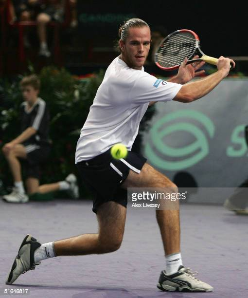 Xavier Malisse of Belgium hits a backhand against Tommy Haas of Germany during the BNP Paribas Masters Event at the Palais Omnisports de Paris-Bercy...