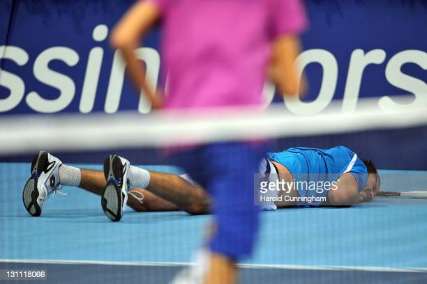 Xavier Malisse of Belgium lays on the floor after falling during his match against Novak Djokovic of Serbia during day two of the Swiss Indoors at St...