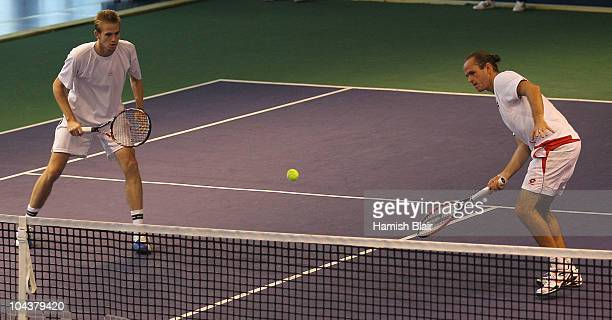 Xavier Malisse of Belgium plays a forehand with team mate Kristof Vliegen of Belgium looking on during their double match against Marcelo Melo and...