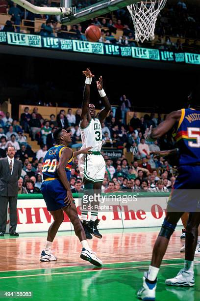 Xavier McDaniel of the Boston Celtics shoots over LaPhonso Ellis of the Denver Nuggets during a game played at the Boston Garden in Boston...