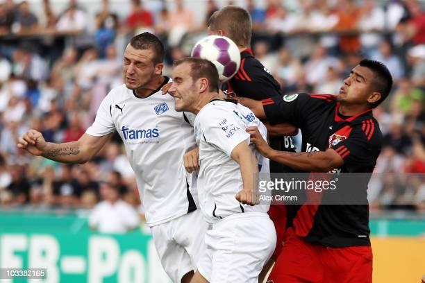 Xavier Novic and Jochen Ellermann of Pirmasens jumps for a header with Lars Bender and Arturo Vidal of Leverkusen during the DFB Cup first round...