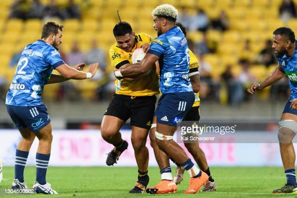 Xavier Numia of the Hurricanes is tackled by Hoskins Sotutu of the Blues during the round one Super Rugby Aotearoa match between the Hurricanes and...