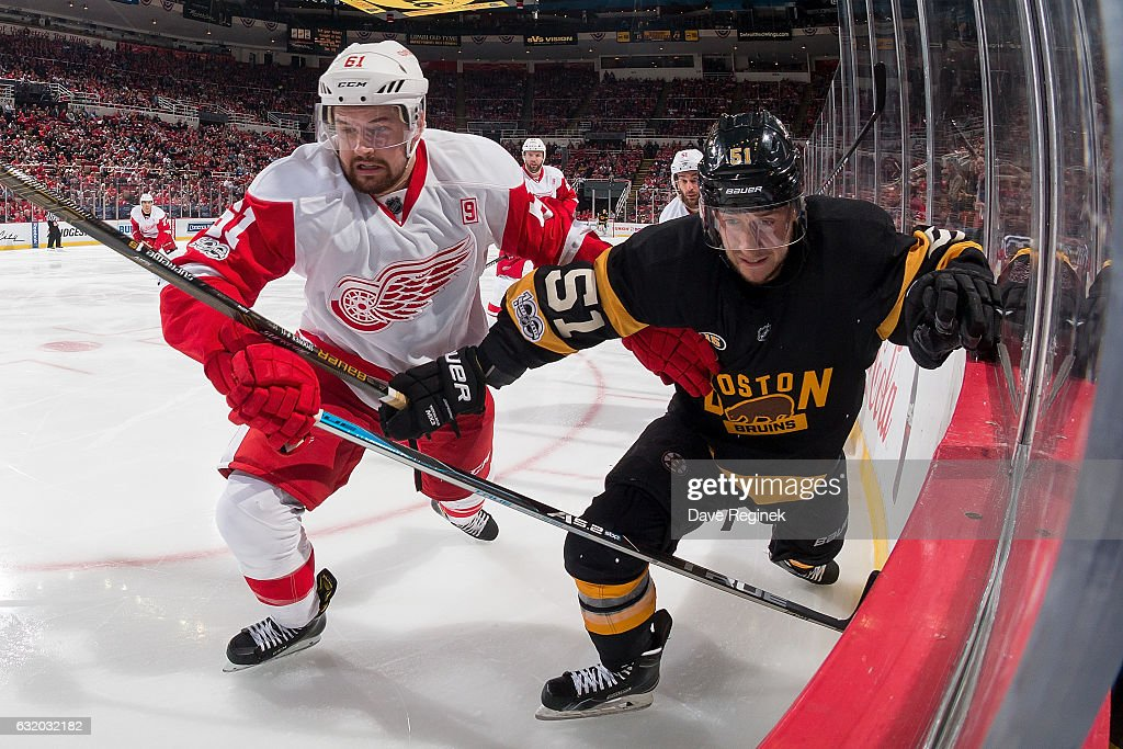 Xavier Ouellet #61 of the Detroit Red Wings battles along the boards with Ryan Spooner #51 of the Boston Bruins during an NHL game at Joe Louis Arena on January 18, 2017 in Detroit, Michigan. The Wings defeated the Bruins 6-5 in a shoot-out.