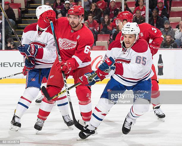 Xavier Ouellet of the Detroit Red Wings battles for position with Andrew Shaw of the Montreal Canadiens during an NHL game at Joe Louis Arena on...