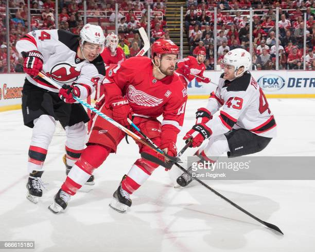 Xavier Ouellet of the Detroit Red Wings battles for the puck with Miles Wood and Ben Thomson of the New Jersey Devils during an NHL game at Joe Louis...