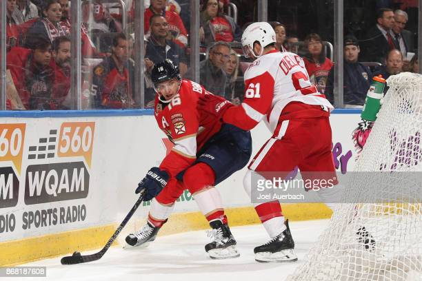 Xavier Ouellet of the Detroit Red Wings defends against Aleksander Barkov of the Florida Panthers as he circles behind the net with the puck at the...