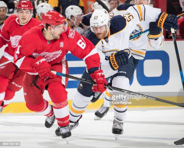 Xavier Ouellet of the Detroit Red Wings skates up ice in front of Hudson Fasching of the Buffalo Sabres during an NHL game at Joe Louis Arena on...