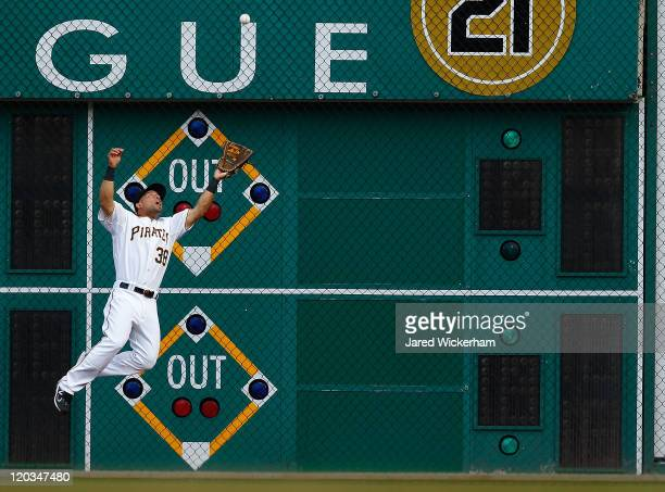 Xavier Paul of the Pittsburgh Pirates jumps up in the air along the warning track to catch a fly ball against the Chicago Cubs during the game on...