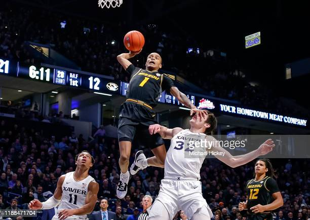 Xavier Pinson of the Missouri Tigers goes up for a dunk attempt as Zach Freemantle of the Xavier Musketeers defends at Cintas Center on November 12,...