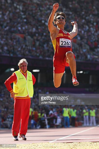 Xavier Porras of Spain is watched by his guide as he competes in the Men's Long Jump - F11 Final on day 6 of the London 2012 Paralympic Games at...