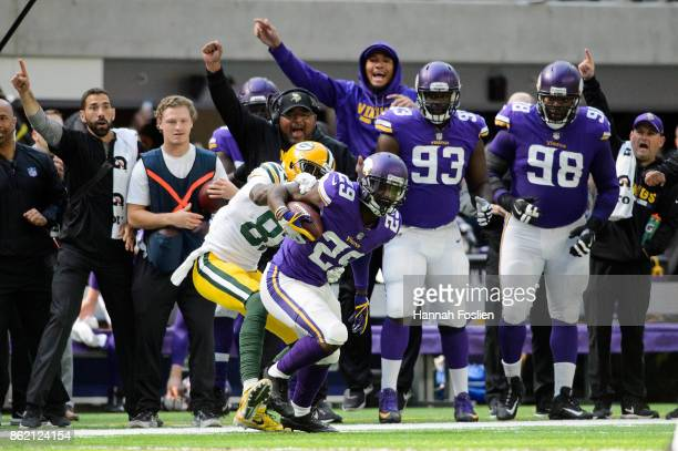 Xavier Rhodes of the Minnesota Vikings carries the ball after an interception as Geronimo Allison of the Green Bay Packers forces him out of bounds...