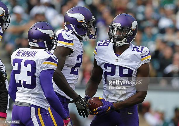 Xavier Rhodes of the Minnesota Vikings celebrates his interception with teammates Terence Newman and Jayron Kearse during the first quarter of a game...