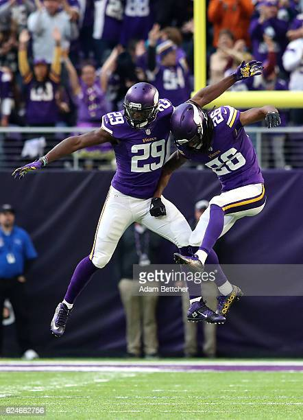 Xavier Rhodes of the Minnesota Vikings celebrates his second interception of the game with teammate Trae Waynes in the third quarter against the...