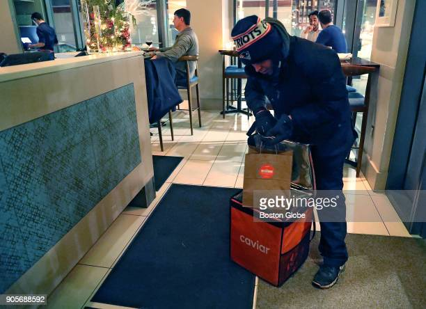 Xavier Rodriguez a delivery person with Caviar picks up a take out meal at Bar Mezzana in Boston on Jan 10 2018 Caviar is a delivery service which...