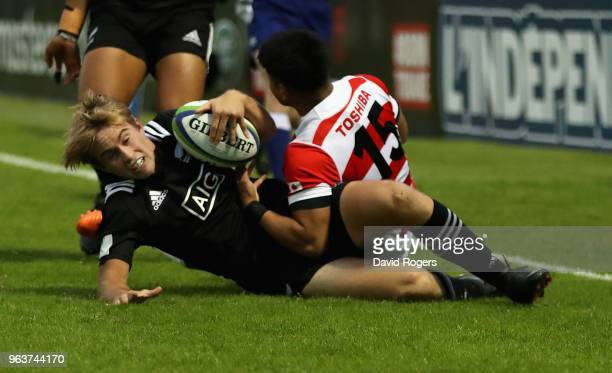 Xavier Roe of New Zealand is tackled during the World Rugby U20 Championship match between New Zealand and Japan at Stade d'Honneur du Parc des...